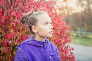 young girl in front of tree